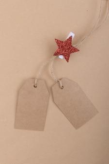 Dwie metki z przetworzonego papieru pakowego zwisające z liny z spinaczem do bielizny z czerwoną gwiazdą bożonarodzeniową na papierze kraft. leżał na płasko
