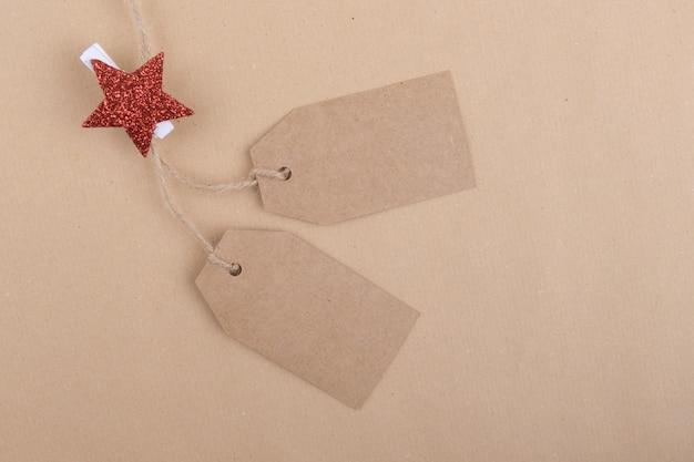Dwie metki z przetworzonego papieru pakowego zwisające ze sznurka ozdobione spinaczem do bielizny z czerwoną gwiazdą bożonarodzeniową