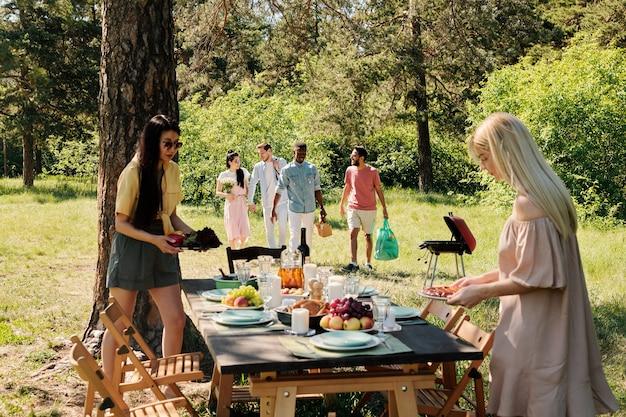 Dwie międzykulturowe dziewczyny serwują stół ze świeżymi owocami i domowym jedzeniem
