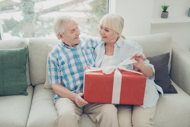 Dwie miłe, wesołe babcie otrzymujące duży romantyczny prezent w jasnobiałym wnętrzu domu z salonem