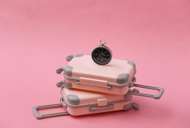 Dwie mini walizki podróżne i kompas na różowo. podróży martwa natura, wakacje lub koncepcja turystyki.