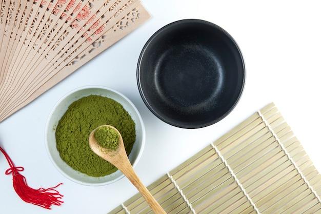 Dwie miseczki do herbaty i bambusowa łyżeczka z proszkiem.