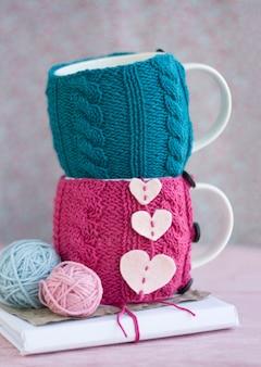 Dwie miseczki w różowo-niebieskim swetrze stoją jedna na drugiej z sercami
