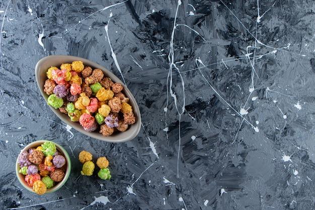 Dwie miski kolorowych smacznych popcornów na marmurowej powierzchni.