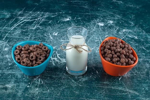 Dwie miski krążków kukurydzianych obok szklanki mleka na niebieskim tle. zdjęcie wysokiej jakości
