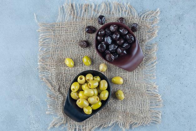 Dwie miski oliwek zielonych i czarnych na marmurowej powierzchni