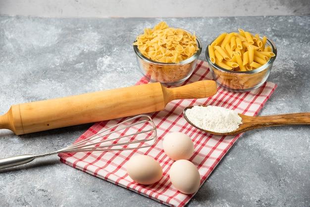 Dwie miski surowego makaronu, jajka, łyżka mąki i wałek do ciasta na marmurowym stole z obrusem.