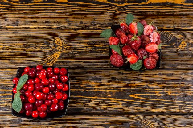 Dwie miski świeżych jagód, jedna wypełniona wiśniami, a druga soczystymi truskawkami, na pyszny zdrowy deser podany na starym drewnianym stole z teksturą z copyspace