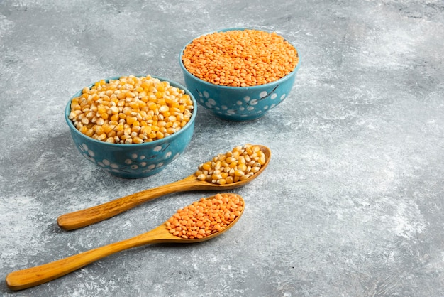Dwie miski ziaren kukurydzy i czerwonej soczewicy na marmurowej powierzchni.