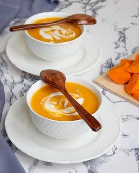 Dwie miski zupy dyniowej na białym tle z szarym materiałem i plasterkami dyni piżmowej