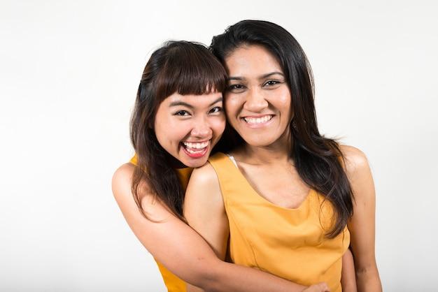 Dwie młode azjatyckie kobiety razem przeciwko białej przestrzeni