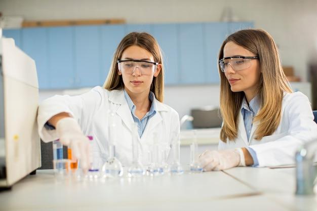 Dwie młode badaczki płci żeńskiej patrząc na kolby z roztworami w laboratorium