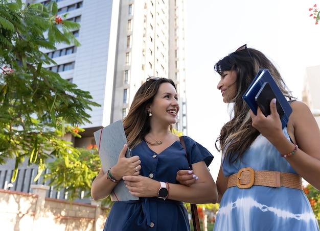 Dwie młode bizneswoman idące ulicą między biurowcami