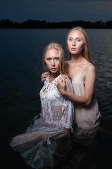 Dwie młode blond bliźniaczki pozują w lekkich sukienkach w wodzie jeziora w letnią noc.