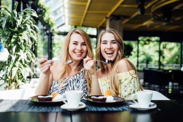 Dwie młode blond siostry jedzą śniadanie w nowoczesnej kawiarni, spędzają razem czas