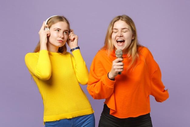 Dwie młode blondynki siostry bliźniaczki dziewczyny w kolorowe ubrania słuchają muzyki w słuchawkach, śpiewają piosenkę w mikrofonie na białym tle na fioletowej niebieskiej ścianie. koncepcja życia rodzinnego osób.
