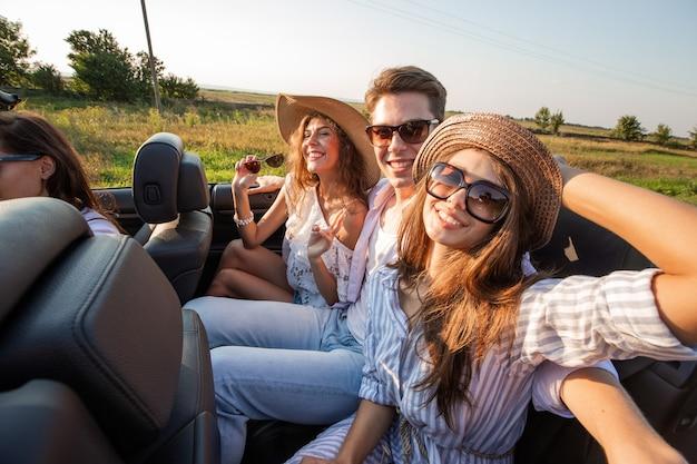 Dwie młode ciemnowłose kobiety w kapeluszach siedzą młodo z mężczyzną w czarnym kabriolecie i uśmiechają się w letni dzień. .