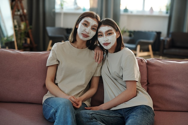Dwie młode, czułe brunetki z glinianą maską na twarzach, siedzące na miękkiej kanapie w środowisku domowym i patrzące na ciebie