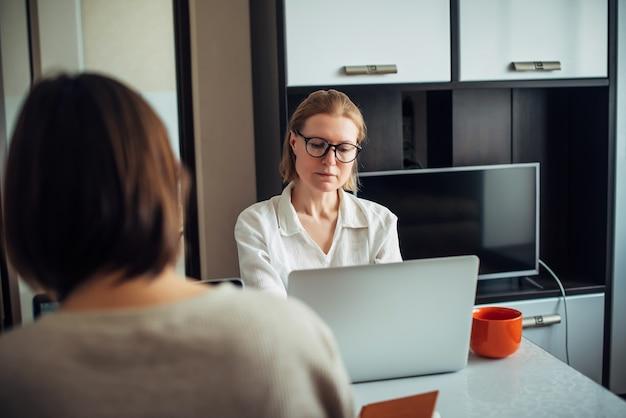 Dwie młode, dorosłe dziewczyny siedzące przy stole naprzeciw siebie, pracujące na laptopach we wnętrzu domu. skoncentruj się na twarzy blondynka w okularach. freelance, coworking, praca zdalna, samozatrudnienie.