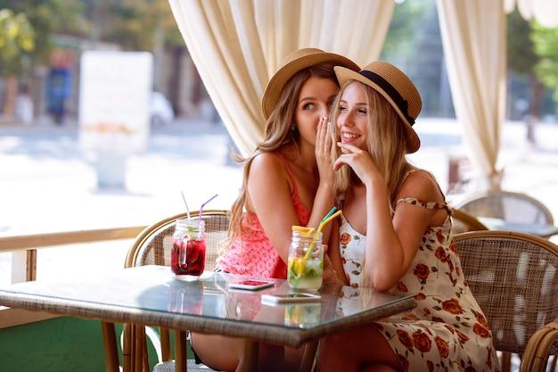 Dwie młode dziewczyny dzielą sekret w uchu, siedząc w kawiarni