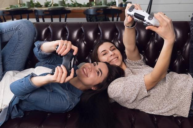 Dwie młode dziewczyny grają na konsoli do gier, radosne kobiety odpoczywają w domu. wysokiej jakości zdjęcie