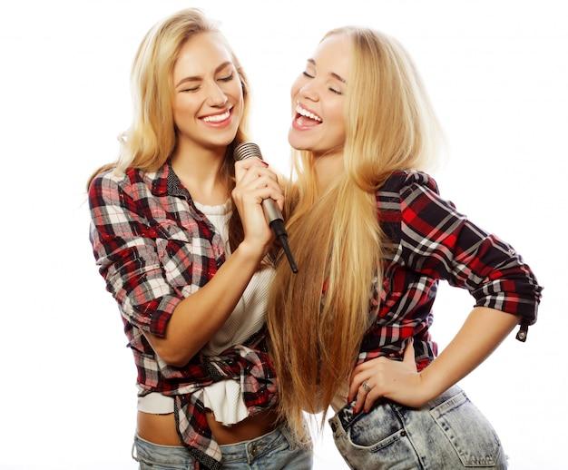 Dwie młode dziewczyny hipster śpiewają