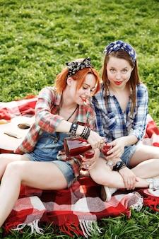 Dwie młode dziewczyny hipster, zabawy na pikniku, koncepcja najlepszych przyjaciół