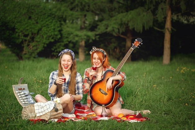 Dwie młode dziewczyny hipster, zabawy na pikniku w letnim parku