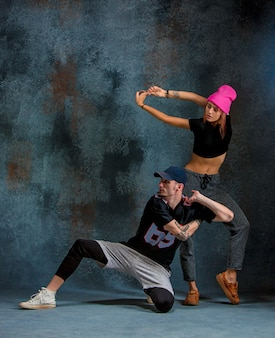 Dwie młode dziewczyny i chłopiec tańczą hip hop w studio