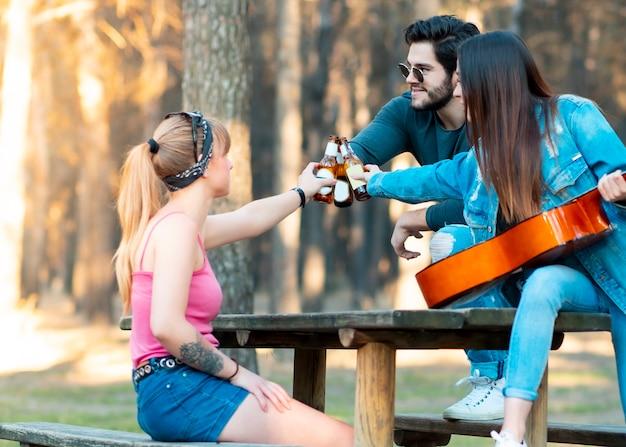 Dwie młode dziewczyny i chłopiec w szklankach piwa grają na gitarze w naturze