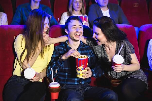 Dwie młode dziewczyny i facet oglądający komedię w kinie