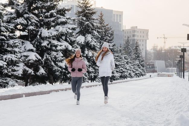 Dwie młode dziewczyny lekkoatletycznego w parku w słoneczny zimowy dzień. zdrowy styl życia.