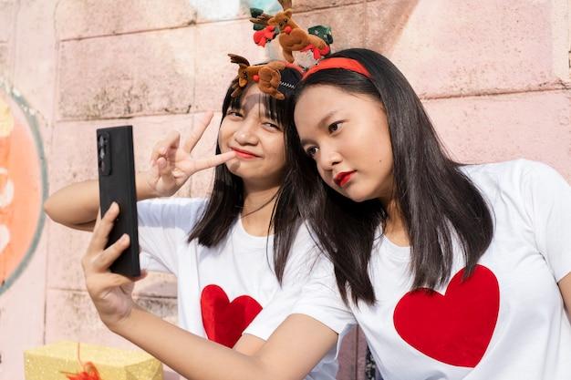 Dwie młode dziewczyny nosić selfie boże narodzenie kapelusz na kolorowe tło.