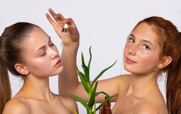 Dwie młode dziewczyny o czystej i nawilżonej skórze. i kwiat aloesu przed twarzami dziewcząt. pojęcie piękna, spa i zdrowia, na białej ścianie. wysokiej jakości zdjęcie