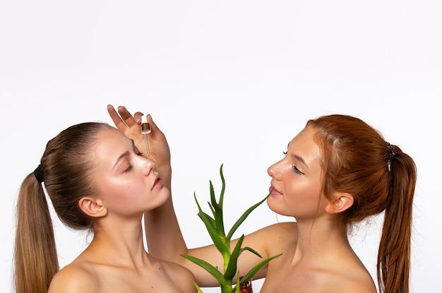 Dwie młode dziewczyny o czystej i nawilżonej skórze. i kwiat aloesu przed twarzami dziewcząt. pojęcie piękna, spa i zdrowia, na białej ścianie. zdjęcie z pustą górną przestrzenią. wysokiej jakości zdjęcie