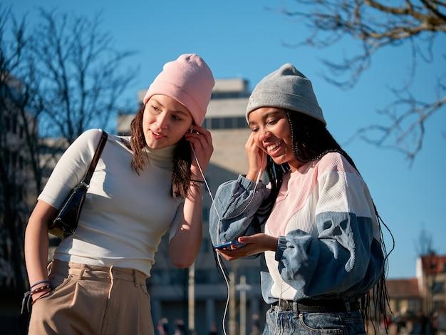 Dwie młode dziewczyny, przyjaciele, słuchają muzyki przez słuchawki smartfona