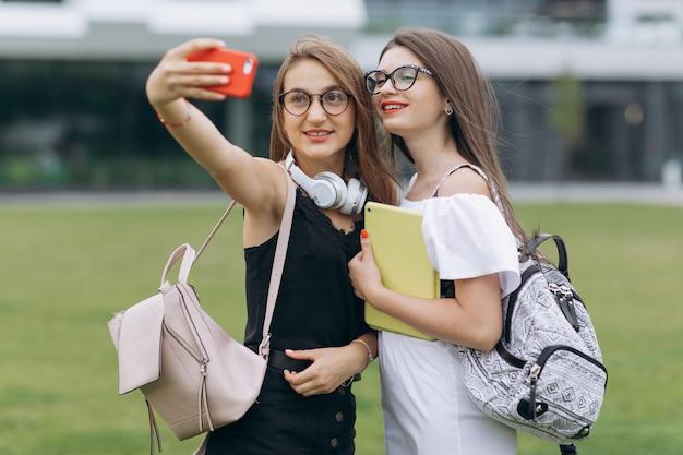 Dwie młode dziewczyny robienia zdjęć autoportretów selfie na smartfonie. kobieta pokazująca pozytywne emocje na twarzy