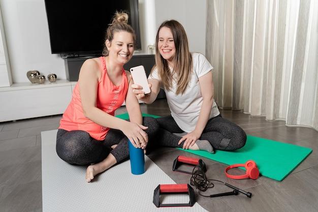 Dwie młode dziewczyny rozmawiają przez rozmowę wideo po uprawianiu sportu w domu.