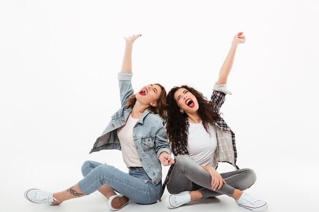 Dwie młode dziewczyny siedzą na podłodze razem krzycząc i patrząc w górę na białej ścianie