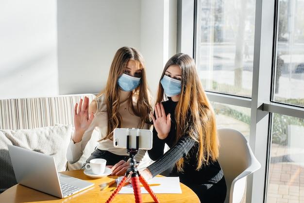 Dwie młode dziewczyny siedzą w kawiarni w maskach i prowadzą wideobloga. komunikacja z aparatem.