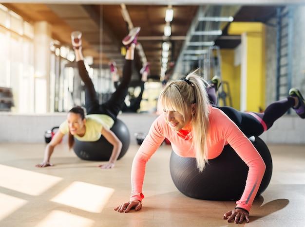 Dwie młode dziewczyny skupione na siłowni wykorzystujące piłki pilates do rozciągania po treningu.