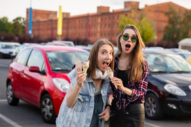 Dwie młode dziewczyny spacerują i jedzą lody w szklance.