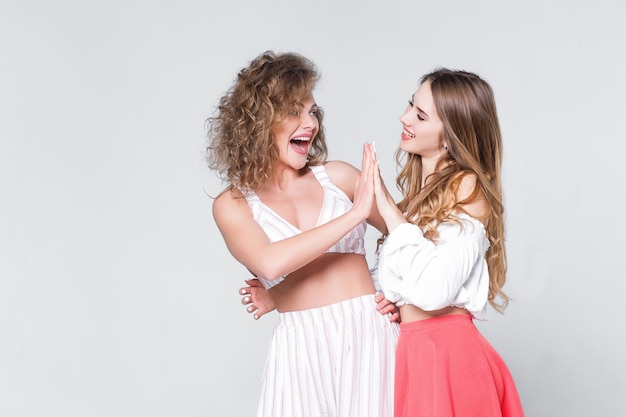Dwie młode dziewczyny stojące razem. patrząc na siebie!