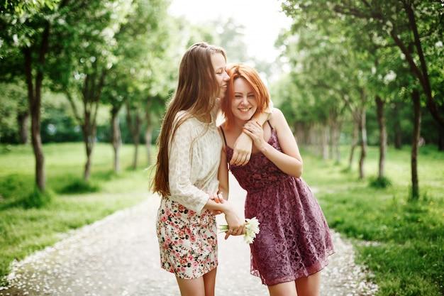 Dwie młode dziewczyny szczęśliwy zabawy w parku