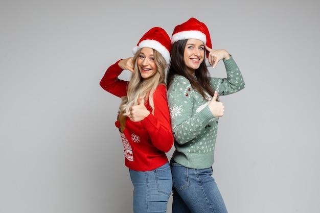Dwie młode dziewczyny w czapkach świętego mikołaja pokazują gest, jakby dzwonili na telefon na szaro