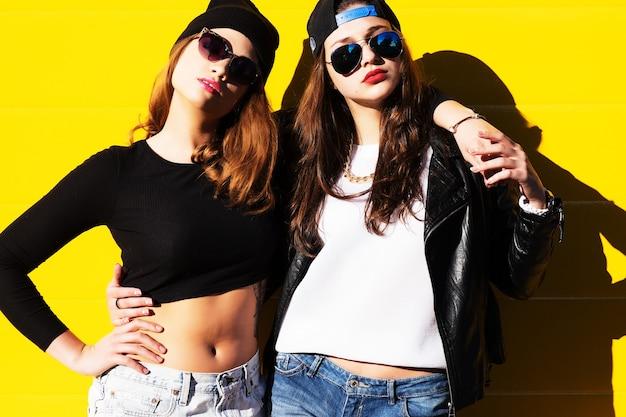 Dwie młode dziewczyny w okularach przeciwsłonecznych, zabawy. styl życia.