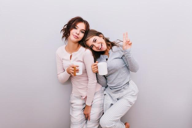 Dwie młode dziewczyny w piżamie z miseczkami na szarej ścianie. dziewczyna z długimi włosami oparł głowę na ramieniu dziewczyny z kręconymi włosami. uśmiechają się.