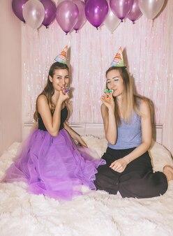 Dwie młode dziewczyny z bliska dwie młode ładne kobiety siedzą na łóżku z fioletowymi kulkami powietrznymi