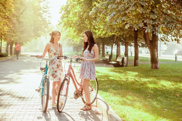 Dwie młode dziewczyny z rowerami w parku