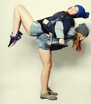 Dwie młode dziewczyny zabawy razem. przytulanie się i uśmiechanie. styl hipsterski.
